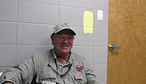 Thumbnail of Dave Peterson sitting with a closed door and concrete wall in the background.