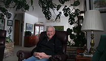 Thumbnail of John Porter is sitting in his living-room in Deer Lodge, MT, he is framed by a plant in surrounding an archway in the background.