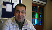 Thumbnail of Pritamsingh Pundis sitting in front of bulletin board with a door behind him.