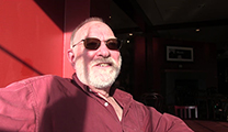 Thumbnail of Scott Richmond is brightly lit by natural light, he is wearing sunglasses and is partially in shadow.