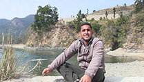 Thumbnail of Bobby Sadpal Sighn sitting outside on the bank of the river with mountains and river bank in the background.
