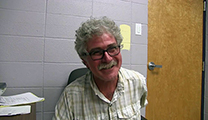 Thumbnail of Scott Sanchez sitting with a closed door and concrete wall in the background.