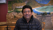 Thumbnail of Karnvir Saran Das sitting in front of a vibrant mural of a landscape with a tiger.