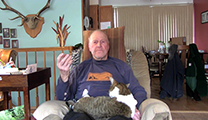 Thumbnail of Tony Schoonen sitting in his livingroom, his diningroom is over one shoulder and a wall with a deer rack over the other shoulder. A cat is sitting on his lap.