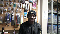 Thumbnail of Trevor Sithole sitting in an outfitting stockroom, with merchandise is being displayed in the background.
