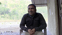 Thumbnail of Alam Soni sitting under an overhang in shadow next to a building surrounded lush greenery behind him.