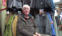 Thumbnail of Bruce Staples sitting in an outfitting store Jimmy's All Seasons Angler in Idaho Falls, Idaho, merchandise is being displayed in the background.