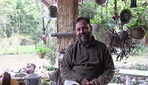 Thumbnail of Ritish Suri sitting under an overhang surrounded by material hanging and lush greenery behind him.