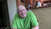 Thumbnail of Doug Swisher sitting at his dining room table with his kitchen in the background.