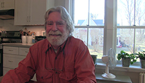 Thumbnail of Gary Tanner sitting in a kitchen with a large window behind him.