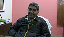 Thumbnail of Amit Verma sitting in an office with a bright pick wall behind him and a corner of a desk to his right.