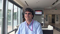 Thumbnail of Alex Vŭlev sitting in a lobby with windows to his right and furniture in the background.