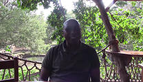 Thumbnail of John Wainaina sitting outside at the Tam Trout and the Trout Tree Restaurant near Nanyuki, Kenya with breeding pools and trees in the background.