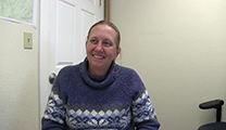 Thumbnail of Mary Kay Watry sitting in small white room with door in the background.