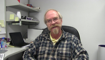 Thumbnail of Joel Weinhold sitting in his office at Denver Outfitters.