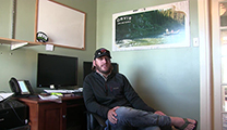 Thumbnail of Kyle Wilkinson sitting in his office in Trous Fly Fishing in Denver, Colorado.