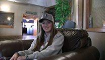 Thumbnail of Olivia Wootan sitting in a large arm chair at a hotel hosting the East Idaho Fly Tiers Expo in Idaho Falls, ID, people walk by in the background.