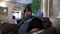 Thumbnail of Shane Wooton sitting in a large arm chair at a hotel hosting the East Idaho Fly Tiers Expo in Idaho Falls, ID, people walk by in the background.