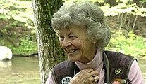 Thumbnail of Joan Wulff sitting under a tree with a stream in the background.