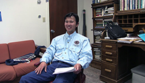 Thumbnail of Satoshi Yamamoto sitting in an office with a old fashion rolltop desk and a couch in the background.