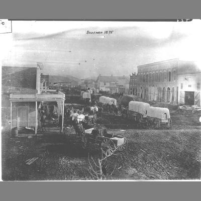Line of Covered Freight Wagons Stretching Down Bozeman Main Street, 1875