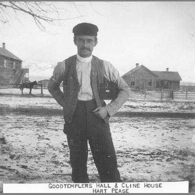 Hart Pease Stands in Front of Good Templars Hall and Cline House