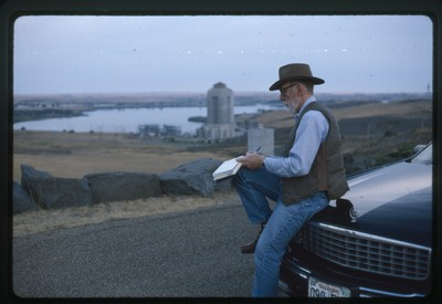 Fort Peck Dam, Montana - Ivan Doig sitting on hood of Cadillac writing