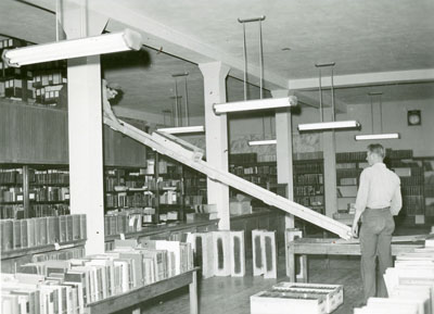 A man unloading boxes from the balcony collection, part of the Library Move 1949/1950