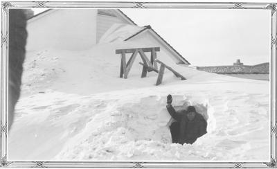 A man in a snow tunnel in the winter, Browning, Montana, 1937
