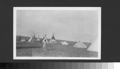 Black and white photo of a young girl standing in an encampment, Alberta, Canada, 1927
